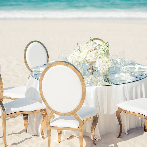 Round table with white tablecloth and mirrored overlay